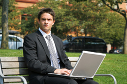 Businessman working on a park bench