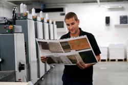 A printer standing next to his press...